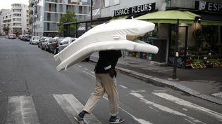 Un migrant porte son matelas sur la rue de Flandres à Paris après l'écvacuation par la police, le 6 septembre 2016 (MATTHIEU ALEXANDRE / AFP)