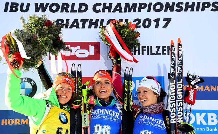 La Tchèque Gabriela Koukalova championne du monde du sprint entourée de l'Allemande Laura Dahlmeier (à gauche) et de la Française Anaïs Chevalier (à droite) peu habituée aux podiums protocolaires. (FRANCK FIFE / AFP)