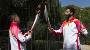 Le skieur grec, Ioannis Antoniou, transmet la flamme olympique à Li Jiajun, ancien patineur de vitesse chinois. (MARIOS LOLOS / XINHUA)
