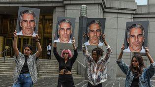 Des manifestantes brandissent le portrait de Jeffrey Epstein devant le tribunal de Manhattan où le milliardaire a comparu, le 8 juillet. (STEPHANIE KEITH / GETTY IMAGES NORTH AMERICA)