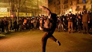 Un manifestant lance un pavé sur les forces de police catalanes à Barcelone ce vendredi 18 février 2021. L'emprisonnement du rapper Pablo Hasél a déclenché des affrontements depuis le 16 février. (JOSEP LAGO / AFP)