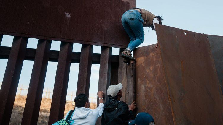 Des migrants sud-américains escaladent un mur à la frontière entre les États-Unis et le Mexique. (ARIANA DREHSLER / MAXPPP)