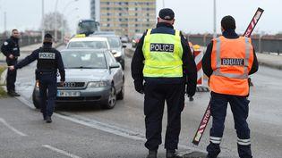 Des officiers de police contrôlent des véhicules à la frontière entre la France et l'Allemagne, le 30 décembre 2017. (FREDERICK FLORIN / AFP)