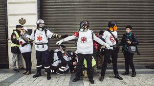 """Des street-medics s'occupent d'un blessé lors d'une manifestation des """"gilets jaune"""" à Paris, le 16 mars 2019. (YANN CASTANIER / HANS LUCAS / AFP)"""