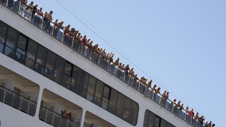"""1 700 personnes, dont un grand nombre de touristes allemands, sont bloquées depuis le 15 mars 2020 sur le bateau de croisière """"AIDAmira"""", dans le port du Cap. Photo prise le 18 mars 2020. (RODGER BOSCH / AFP)"""