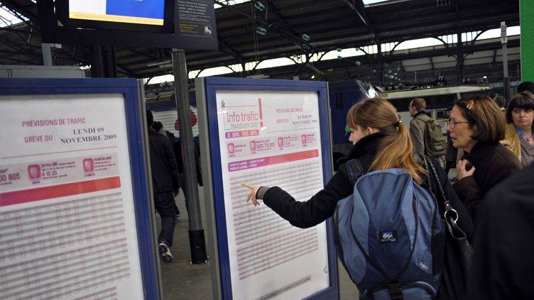 Des usagers consultent un tableau d'informations, le 9 novembre 2009 gare Saint-Lazare, à Paris. (FRED DUFOUR / AFP)