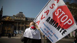 """Un manifestant brandit un drapeau """"Stop Amiante"""" devant le palais de justice de Paris, le 22 mars 2019, à l'occasion de l'examen de la demande de reconnaissance du """"préjudice d'anxiété"""" d'anciens salariés d'EDF. (THOMAS SAMSON / AFP)"""