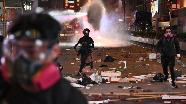 Des manifestants courent alors que la police déploie les canons à eau, dans le quartier de Mong Kok, à Hong Kong, le 11 novembre 2019. (PHILIP FONG / AFP)