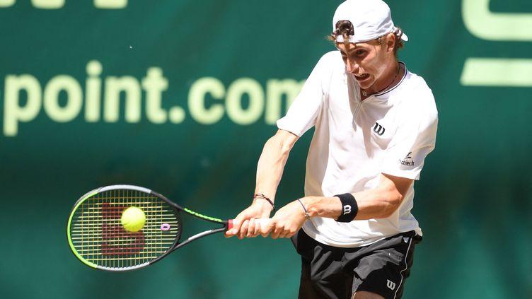 Le Français Ugo Humbert rend le ballon à Felix Auger-Aliassime lors de leur match de demi-finale du tournoi de tennis ATP 500 Halle Open à Halle, en Allemagne, le 19 juin 2021. (CARMEN JASPERSEN / AFP)