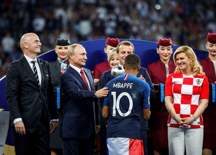 Le président français Emmanuel Macron, l'ancienne présidente croate Kolinda Grabar Kitarovic (à d.), le président russe Vladimir Poutine et le président de la FIFA Gianni Infantino (à g.) saluent le français Kylian Mbappé lors de la cérémonie de remise des prix lors de la finale de la Coupe du monde 2018, après la victoire de la France face à la Croatie, à Moscou, le 15 juillet 2018.   (SEBNEM COSKUN / ANADOLU AGENCY)