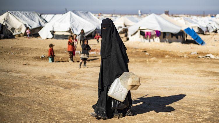 Une femme transporte des jerrycans vides dans le camp géré par les Kurdes d'Al-Hol, dans le nord-est de la Syrie, le 14 janvier 2020. (DELIL SOULEIMAN / AFP)