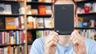 Un homme lisant un e-book dans une librairie en Allemagne, en janvier 2012. (KIEFER / VARIO IMAGES / SIPA)