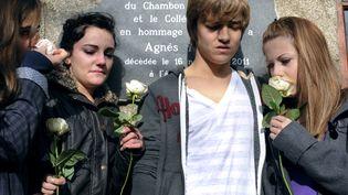 Des camarades d'Agnès, collégienne de 13 ans violée et assassinée le 16 novembre 2011, se recueillent devant une plaque en sa mémoire, le 20 novembre 2011, au collège Cévenol du Chambon-sur-Lignon (Haute-Loire). (PHILIPPE DESMAZES / AFP)