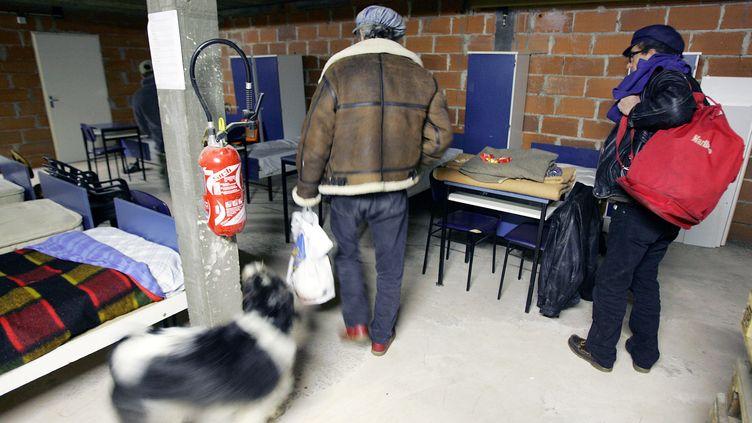Deux SDF arrivent dans un centre d'accueil de Cahors (Lot), le 28 décembre 2005. (GEORGES GOBET / AFP)