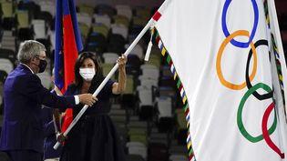 Le président du CIO, Thomas Bach, transmet le drapeau olympique à Anne Hidalgo, maire de Paris, le 8 août 2021. (JAE C. HONG / AP)