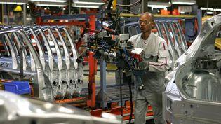 Un ouvrier de l'usine PSA de Mulhouse (Haut-Rhin) travaille sur une chaîne de montage, le 11 juin 2009. (DENIS SOLLIER /L'ALSACE / MAXPPP)