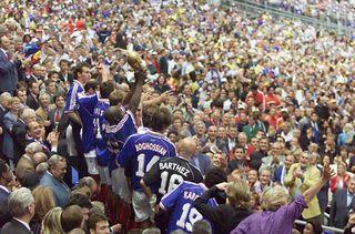 Les joueurs de l'équipe de France brandissent la Coupe du monde, dans la tribune présidentielle du Stade de France, le 12 juillet 1998. (JACQUES DEMARTHON / AFP)