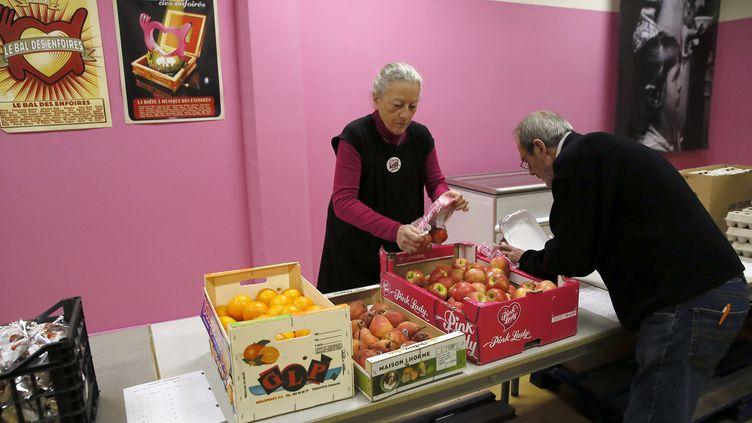Des bénévoles des Restos du cœur préparent une distribution de repas à Paris, le 25 novembre 2013. (PATRICK KOVARIK / AFP)