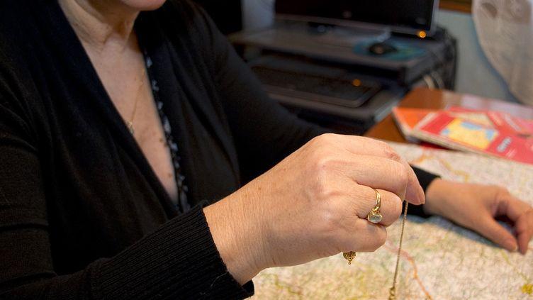 Une cartomancienne utilise un pendule au dessus d'une carte de France le 22 décembre 2011 au Vernet (Haute-Garonne). (PASCAL PAVANI / AFP)