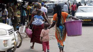 Des femmes et des enfants passent devant les étals du marché de Port-Gentil, au Gabon, le 18 janvier 2017. (JUSTIN TALLIS / AFP)