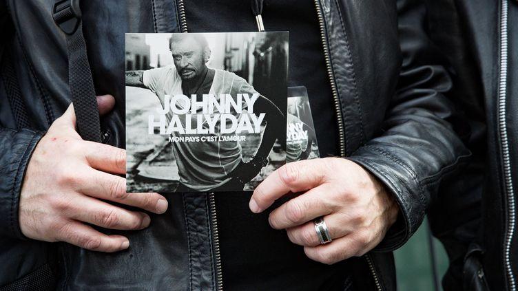 La couverture de l'album posthume de Johnny Hallyday lors d'une conférence de presse de présentation, le 15 octobre 2018. (GEOFFROY VAN DER HASSELT / AFP)