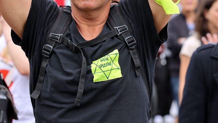 """Un homme porte une étoile jaune sur laquelle est inscrite """"non vacciné"""" lors d'une manifestation contre l'extension du pass sanitaire à Paris, le 17 juillet 2021. (MAXPPP)"""