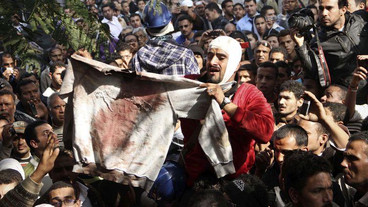 Un manifestant égyptien brandit un vêtement présenté comme étant celui d'une victime des violences policières, près de la place Tahrir du Caire (Egypte), le 19 décembre 2011. (AP / SIPA)
