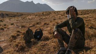 Un migrant afghan attend des passeurs à l'est de la Turquieaprès avoir traversé à pied la frontière avec l'Iran, en août 2021. Photo d'illustration. (OZAN KOSE / AFP)