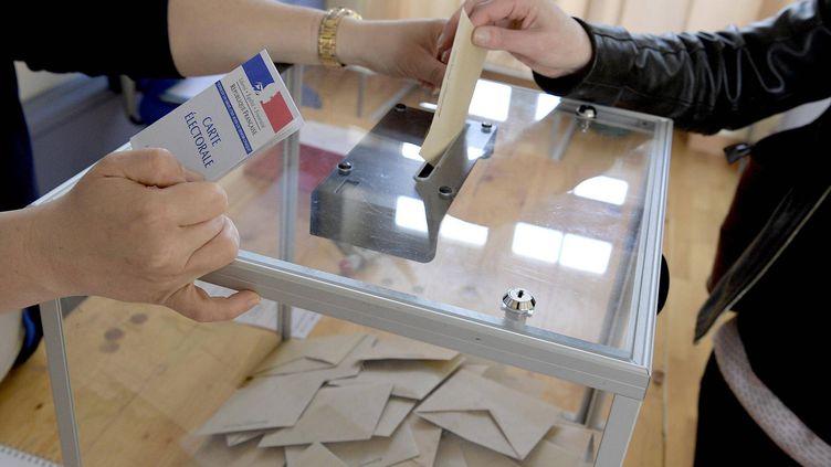 Une personne dépose son bulletin de vote dans l'urne. (Photo d'illustration) (MAXPPP)
