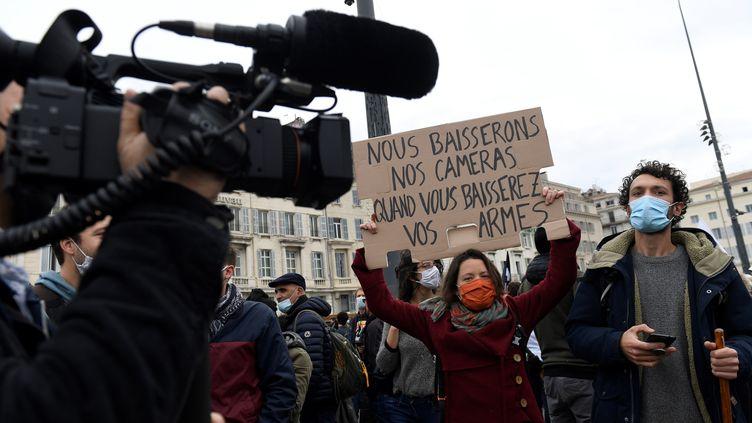 """Une manifestante tient un panneau à Marseille, lors d'une manifestation contre les violences policières et la proposition de loi sur la """"sécurité globale"""",le 28 novembre 2020. (NICOLAS TUCAT / AFP)"""
