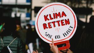 """Une pancarte """"Sauvez le climat"""" lors d'une manifestation à Cologne (Allemagne) le 19 mars 2021. (YING TANG / NURPHOTO / AFP)"""