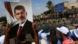 Un partisan des Frères musulmans brandit une pancarte avec la photo du président déchu Mohamed Morsi lors d'une manifestation au Caire (Egypte), le 19 juillet 2013. (MARWAN NAAMANI / AFP)