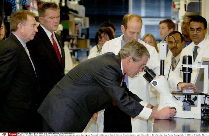 Le président américain George W. Bush observe le virus Ebola au microscope, le 3 février 2003, à Bethesda (Maryland). Nancy Sullivan apparaît au second plan, au centre. (PABLO MARTINEZ MONSIVAIS/AP/SIPA)