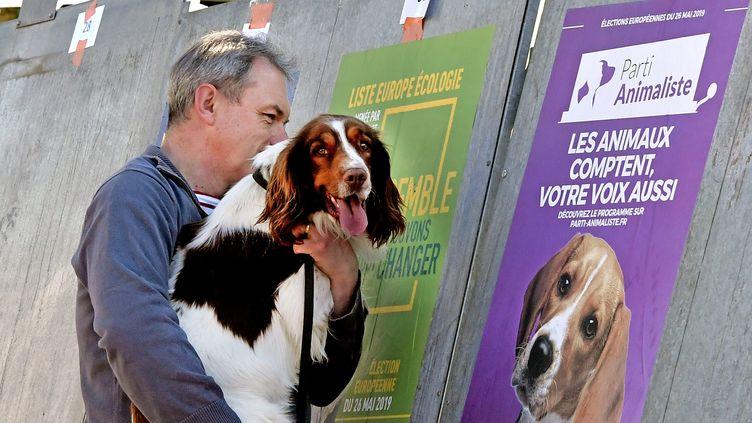 Un homme et son chien observent une affiche du Parti animaliste pour les élections européennes, le 22 mai 2019 à Lyon. (MAXPPP)