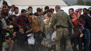 Un policier macédonien maintient la foule des migrants dans le camp près de la ville de Gevgelija, à la frontière gréco-macédonienne, le 7 septembre 2015. (STOYAN NENOV / REUTERS)