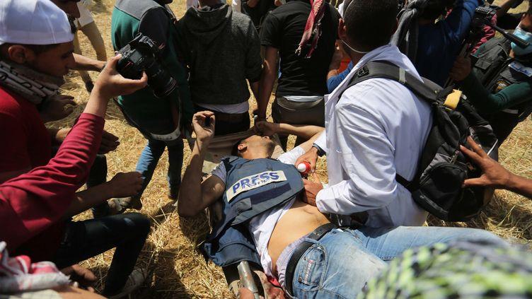 Yasser Mourtaja, un journaliste palestinien, transporté le 6 avril 2018, après avoir été mortellement blessé par balles par des soldats israéliens, lors d'une manifestation près de Khan Younès, dans la bande de Gaza. (ASHRAF AMRA / ANADOLU AGENCY / AFP)