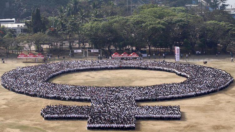 Des manifestants forment le symbole du genre féminn à l'occasion de la Journée internationale des droits des femmes, le 8 marqs 2014, à Manille (Philippines). (ROMEO RANOCO / REUTERS)