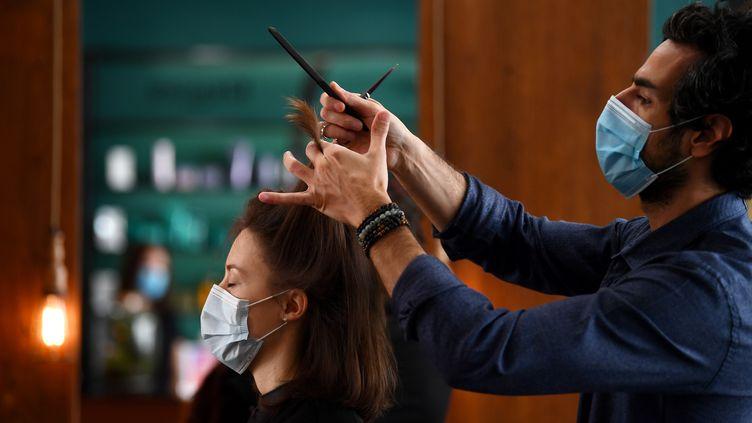 Une femme se fait couper les cheveux dans un salon de coiffure à Paris, le 12 mai 2020. (FRANCK FIFE / AFP)