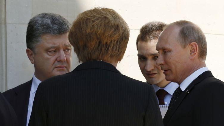 Le président ukrainien, PetroPorochenko (G), la chancelière allemande Angela Merkel (de dos), et le président russe, VladimirPoutine (D) discutent en marge des cérémonies de commémoration du D-Day, au château de Bénouville (Calvados), le 6 juin 2014. (KEVIN LAMARQUE / REUTERS)