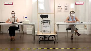 Masques, visières, parois en plexiglas : un dispositif sanitaire complet était mis en place dans ce bureau de vote parisien, le 28 juin 2020, pour le second tour d'élections municipales perturbées par la crise sanitaire. (BERTRAND GUAY / AFP)