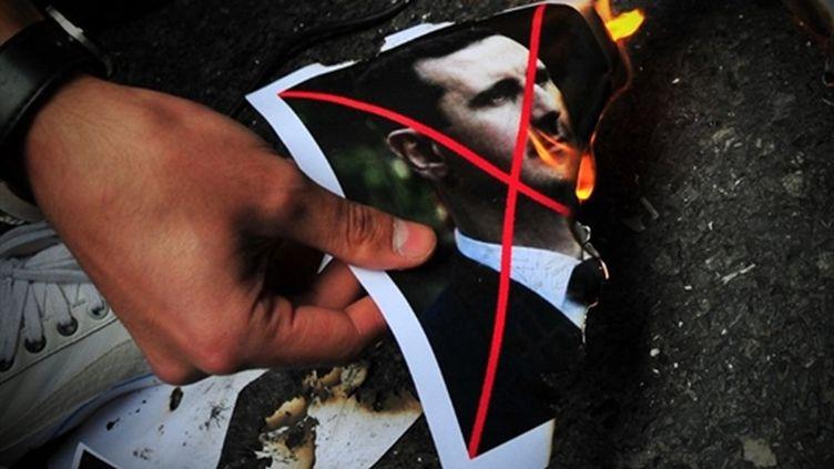 Un manifestant brûle une photo de Bachar el-Assad devant la consulat de Syrie à Istanbul (AFP / Mustafa Ozer)