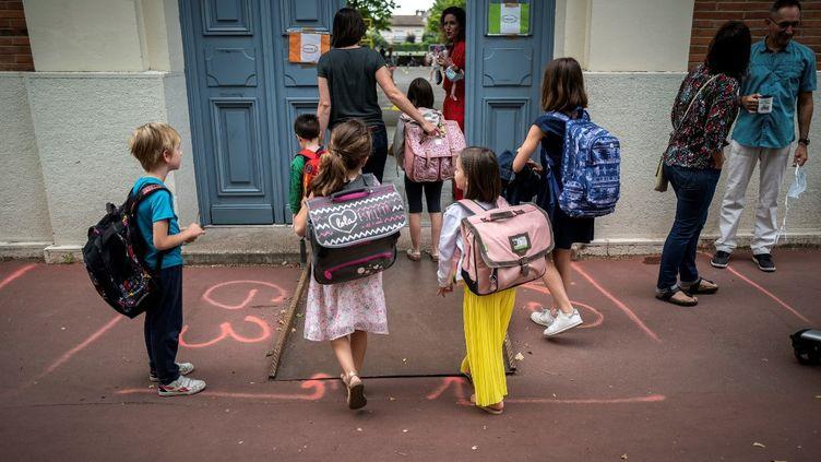 Des enfants à l'entrée d'une école élémentaire à Toulouse, le 22 juin 2020. (LIONEL BONAVENTURE / AFP)