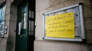 Une affiche annonçant la fermeture d'une école à partir du lundi 16 mars 2020, à Paris. (MARTIN NODA / HANS LUCAS / AFP)
