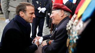 Emmanuel Macron, discutant avec un ancien combattant, le 8 mai 2019 à Paris. (CHRISTIAN HARTMANN / AFP)