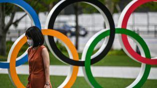 Une femme portant un masque devant les anneaux olympiques à Tokyo, le 24 août 2020. (CHARLY TRIBALLEAU / AFP)