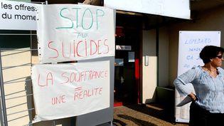 Une employée de France Télécom, devant l'entréed'un bureau de l'entreprise, à Annecy-le-Vieux, où travaillait un salarié qui s'est suicidé, le 28 septembre 2009. (JEAN-PIERRE CLATOT / AFP)