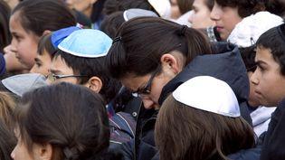 Des élèves de l'école juive Gan-Rachi à Toulouse (Haute-Garonne) observent, le 20 mars 2012, une minute de silence à la mémoire des victimes tuées au collège-lycée juif Ozar Hatorah,la veille. (PASCAL PAVANI / AFP)