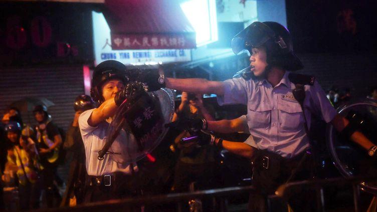 Un policier pointe une arme à feu lors d'une manifestation à Hong Kong, le 25 août 2019. (LILLIAN SUWANRUMPHA / AFP)