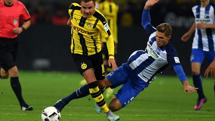 Le meneur de jeu du Borussia Dortmund, Mario Götze, évite ici le tacle du défenseur berlinois, Niklas Stark. (PATRIK STOLLARZ / AFP)