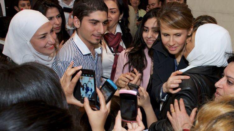 La femme du président syrien Bachar Al-Assad, Asma Al-Assad, entourée de jeunes Syriens le 17 mars 2013 à l'opéra de Sydney, sur une image fournie par la présidence syrienne. (SYRIAN PRESIDENCY MEDIA OFFICE / AFP)